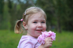 Happy little girl in the garden holding a bouqet of flowers Stock Photo
