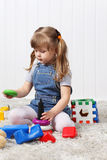 Happy little girl gathers pyramid among toys Stock Images