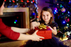 Happy little girl getting a Christmas gift from her mommy Royalty Free Stock Images
