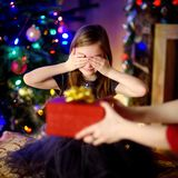 Happy little girl getting a Christmas gift from her mommy Stock Image