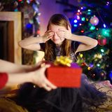 Happy little girl getting a Christmas gift from her mommy Stock Photography