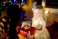 Happy little girl getting a Christmas gift from her mommy Stock Photos