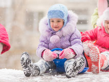 Happy little girl getting ready to roll down the icy hill. Two girls in the winter ride on a snowy hill surrounded by other children Royalty Free Stock Images