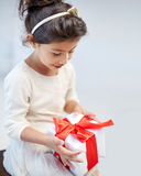 Happy little girl with gift box at home Royalty Free Stock Image