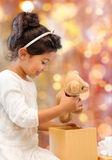 Happy little girl with gift box and teddy bear Stock Image