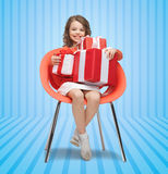Happy little girl with gift boxes sitting on chair Royalty Free Stock Photography