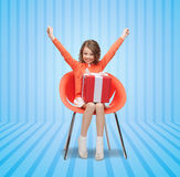 Happy little girl with gift boxes sitting on chair Stock Photography