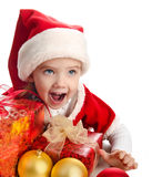 Happy little girl with gift christmas boxes balls and hat Royalty Free Stock Images