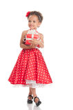 Happy little girl with a gift in mulatta hands Royalty Free Stock Images
