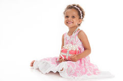 Happy little girl with a gift in mulatta hands Stock Images