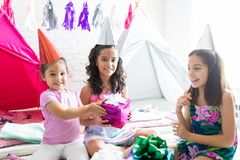 Happy Girl Giving Birthday Present To Friend During Pajama Party. Happy little girl giving birthday present to friend during pajama party at home stock image