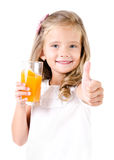 Happy little girl with glass of juice and finger up Stock Photos