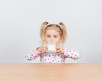 Happy little girl with a glass of milk. Royalty Free Stock Photo