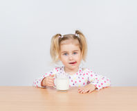 Happy little girl with a glass of milk. Royalty Free Stock Image