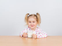 Happy little girl with a glass of milk. Royalty Free Stock Photography