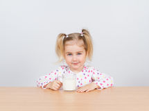 Happy little girl with a glass of milk. Stock Photography