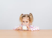 Happy little girl with a glass of milk. Royalty Free Stock Photos