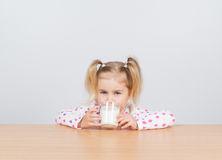 Happy little girl with a glass of milk. Stock Photos
