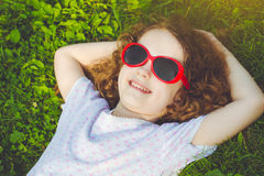 Happy little girl with glasses lying on the grass in a summer pa Stock Photos