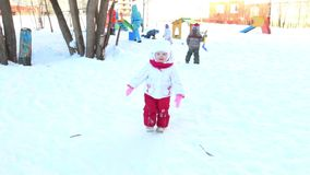 Happy little girl goes and boy plays with shovel on playground at winter sunny day stock video