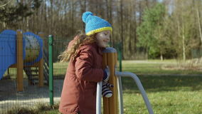 Happy little girl in good mood playing on the playground. Female turning on the carousel and smling. Carefree childhood. stock video footage