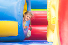Happy little girl got out of inflatable soft barrel while playing on the trampoline. Happy little girl got out of the inflatable soft barrel while playing on the Stock Images