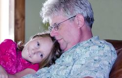 Happy little girl with grandpa. A smiling little girl spends time cuddeling with her grandpa. qaulity time bonding with senior family members Stock Photography