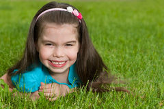 Happy little girl on the grass Stock Image