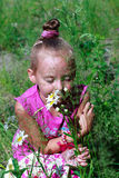Happy little girl in grass smelling daisies Royalty Free Stock Photography