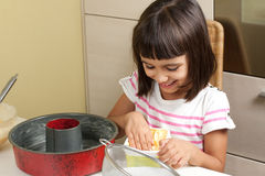 Happy little girl greasing a mold to bake a cake Stock Photos