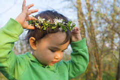 Happy little girl in green with flowers wreath Stock Photos