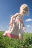 Happy little girl on green meadow Stock Photo