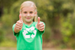 Happy little girl in green with thumbs up Stock Images