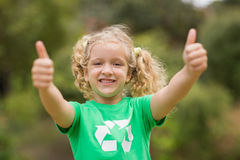 Happy little girl in green with thumbs up Stock Image