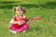 Happy little girl with guitar Stock Photos