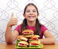 Little girl with hamburgers and thumb up Royalty Free Stock Photo