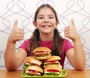 Little girl with hamburgers and thumbs up Royalty Free Stock Images