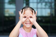 Happy little girl with hands glasses in front of her eyes stock photography
