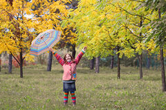 Happy little girl with hands up and umbrella autumn seas Royalty Free Stock Photos