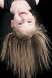 Happy little girl hanging upside down isolated on Stock Photography