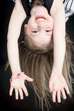 Happy little girl hanging upside down isolated on Royalty Free Stock Photo