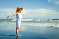 Happy little girl in the hat  standing at the beach in the day t Royalty Free Stock Photos