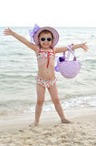 Happy little girl in a hat and sunglasses posing on the beach. Royalty Free Stock Images