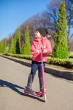Happy little girl have fun on the scooter in warm spring day Royalty Free Stock Photo