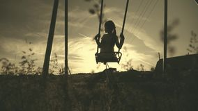 Happy little girl have fun sway spin on a swing on nature sunset. A silhouette young girl swings on a swing. stock video footage