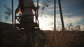 Happy little girl have fun sway spin on a swing on nature sunset. A silhouette young girl swings on a swing. Happy little girl have fun sway spin on a swing on stock video