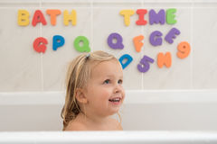 Happy little girl having a bath. Smiling little girl in bathroom with colorful foam letters and numbers in background. Water fun for kids Stock Photo