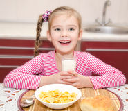 Happy little girl having breakfast drinking milk Stock Photography