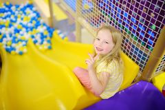 Happy little girl having fun in ball pit in kids indoor play center. Child playing with colorful balls in playground ball pool. Activity toys for little kids Royalty Free Stock Photos
