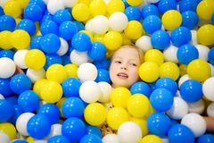 Happy little girl having fun in ball pit in kids indoor play center. Child playing with colorful balls in playground ball pool. Stock Photography